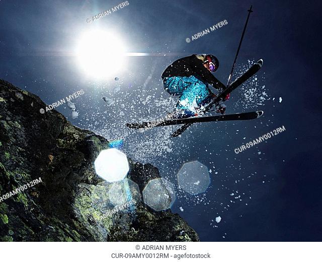 Female skier jumping over rock