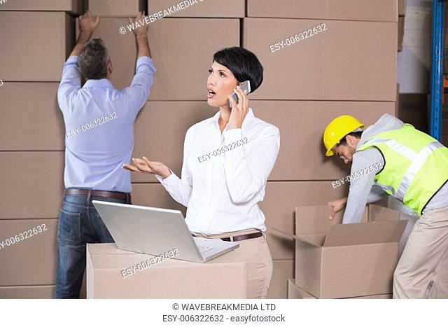 Warehouse manager using laptop and talking on phone in a large warehouse
