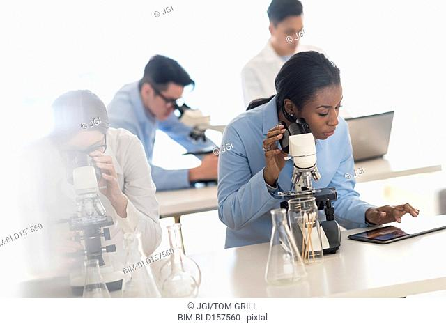 Scientists using microscopes and digital tablet in research laboratory