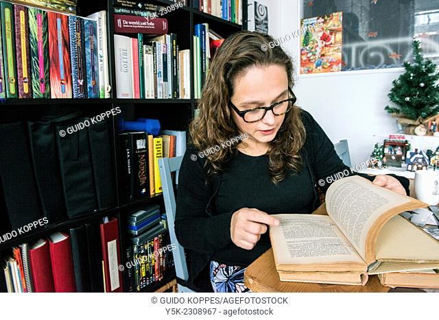 Tilburg, Netherlands. Young, single, and thoughtful woman with her library of books in her living room