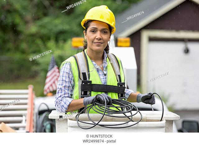 Hispanic female cable lineman in lift bucket
