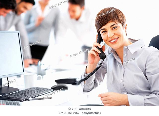 Happy business woman on telephonic conversation with colleagues in background