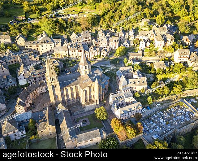 Aerial view of the medieval village of Conques in France. It shows visitors its abbey-church and clustered houses topped by slate roofs