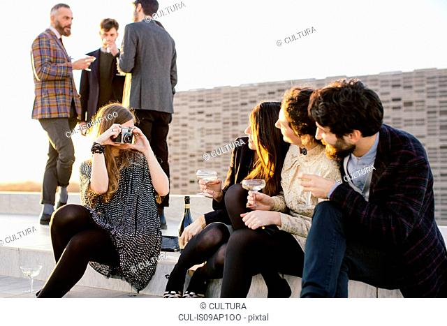 Woman taking photograph of friends at party