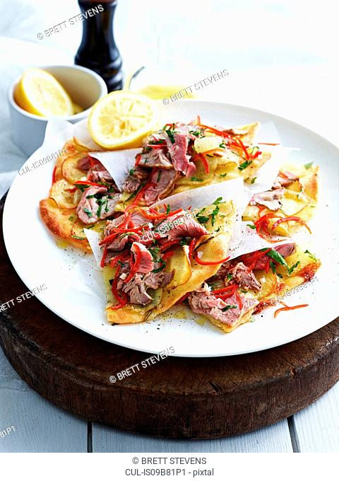 Sliced roast lamb and potato pizza on white plate