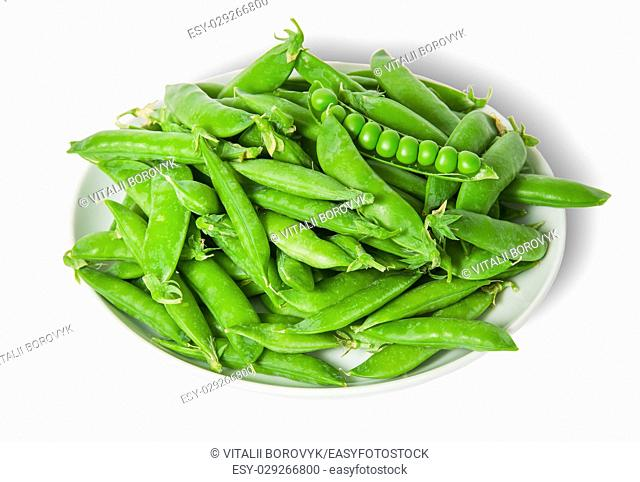 Big pile opening and closing pea pods on white plate isolated on white background