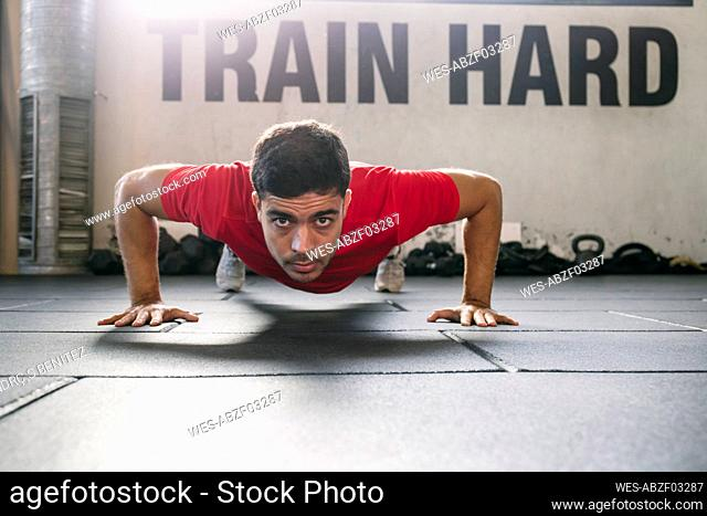 Confident male athlete practicing push-ups on floor in gym