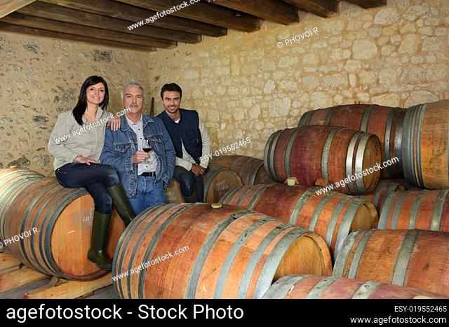three people drinking wine in a cellar