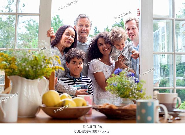 Portrait of family standing at patio doors, ready for breakfast