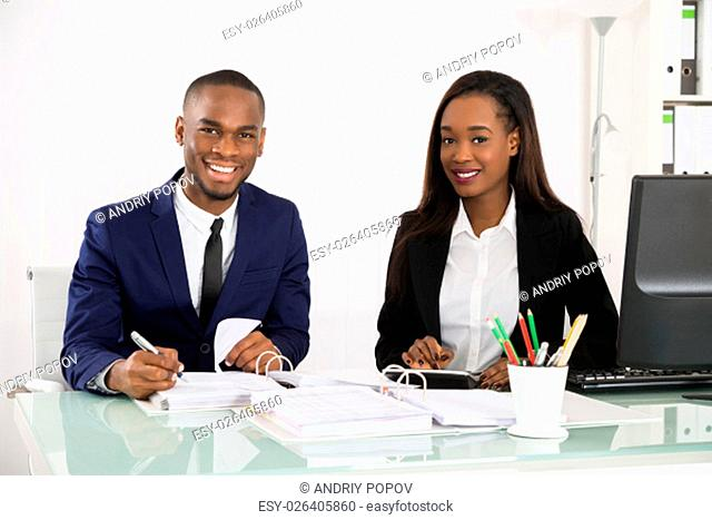 Two Happy Businesspeople Working On Business Document At Office