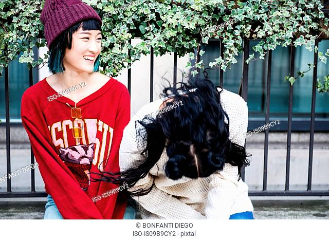 Two young stylish women laughing on city bench