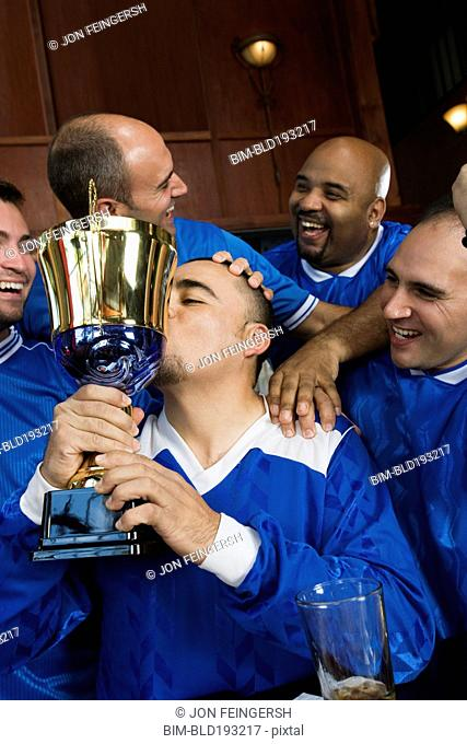 Cheering teammates and man kissing trophy