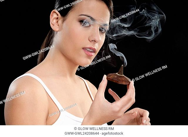 Woman smelling a burning incense cone