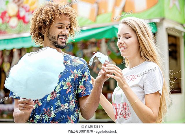 Young couple eating candy floss at a fun fair