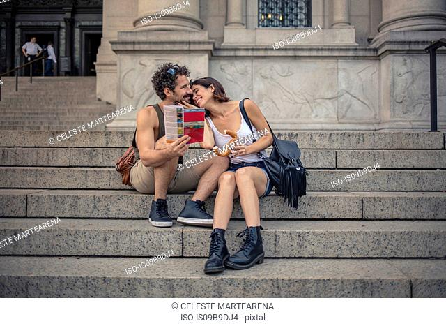 Laughing tourist couple sitting on stairway with map, Manhattan, New York, USA