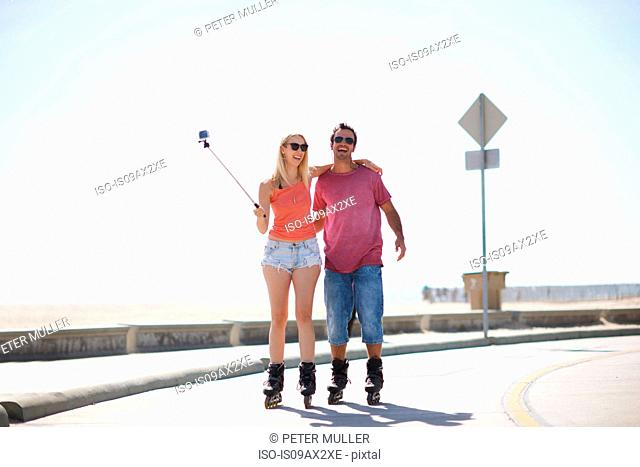 Couple rollerblading outdoors, woman holding selfie stick