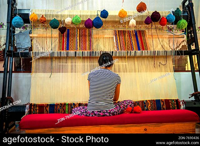 CAPPADOCIA - MAY 17 : Woman working at the manufacture of carpets, on May 17, 2013, in Cappadocia, Turkey. Turkish rugs are one of the main economic sectors of...