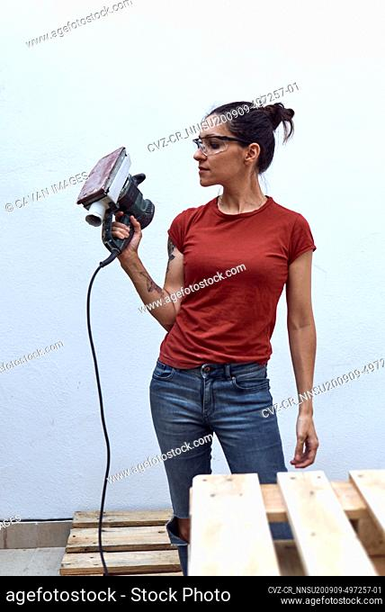 young woman with a power sander on a white background