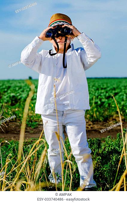 Cute trendy little boy in a stylish hat standing in farmland using binoculars to survey the countryside, frontal view against a field of green crops and blue...