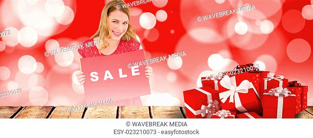 Composite image of smiling blonde showing a red sale poster