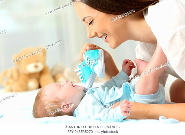 Happy mother showing a new shoes to her baby on a bed at home