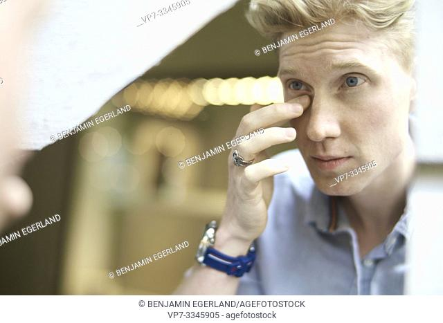 young man checking his appearance in mirror, eye circles