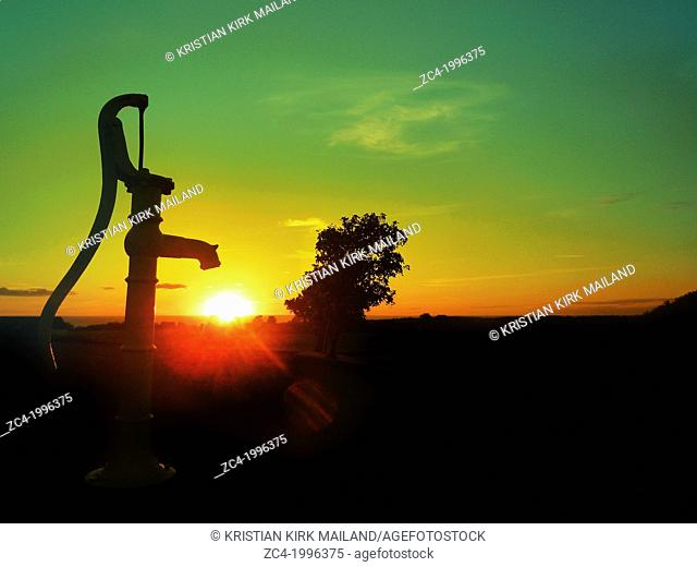 Old water pump. Sunset over the horizon of the sea