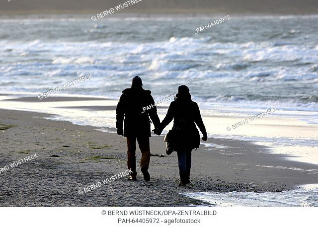 Strollers walk hand in hand on the beach of Rostock-Warnemuende, Germany, 12 December 2015. Northern Germany experienced partly cloudy but mild weather