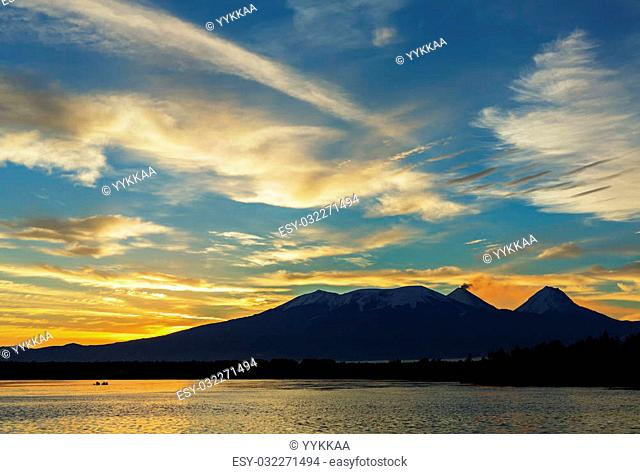 Beautiful sunrise over the volcanoes Kluchevskaya group with reflection in the river Kamchatka