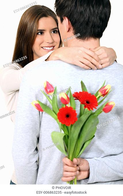 Man with surprise flowers for his girlfriend