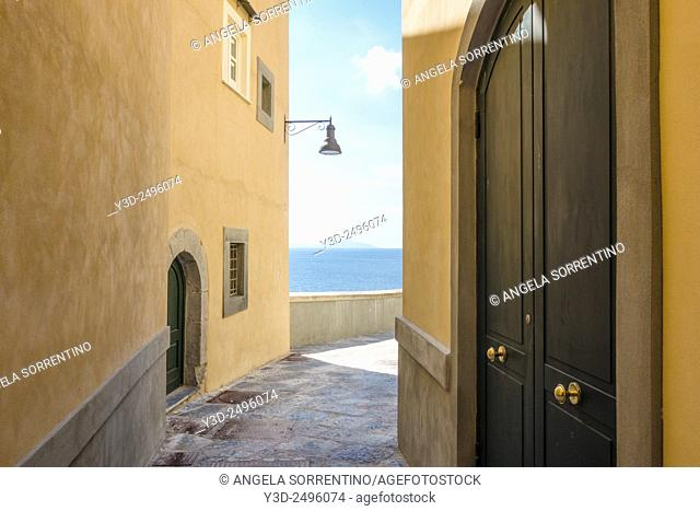 Alley in Pozzuoli with view of blue sea and Capri island at the horizon