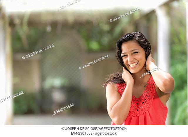 19 year old brunette woman wearing a dress smiling at the camera, outdoors