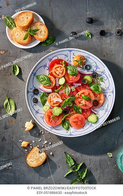 Salad of tomatoes, cucumbers, green peppers, olives, onions with basil and oregano served with croutons. Salad on white plates with blue patterns
