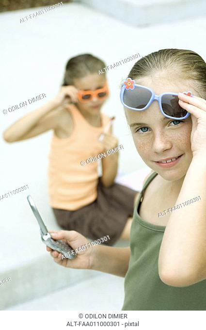 Girl lifting sunglasses and holding cell phone