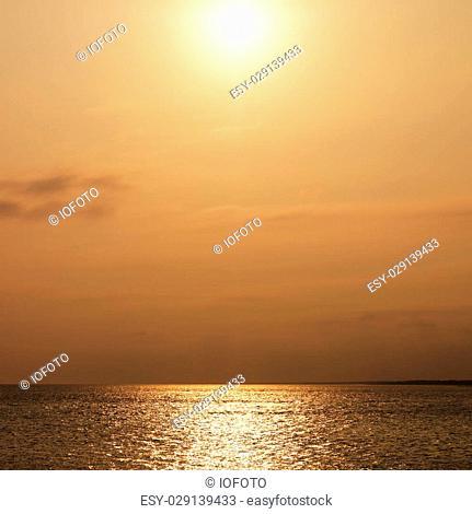 Sun over ocean with warm red tones