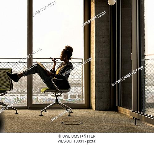 Businesswoman sitting on office chair using cell phone
