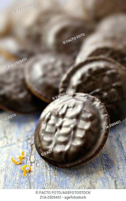 Jaffa cakes with orange garnishes on a blue wooden table