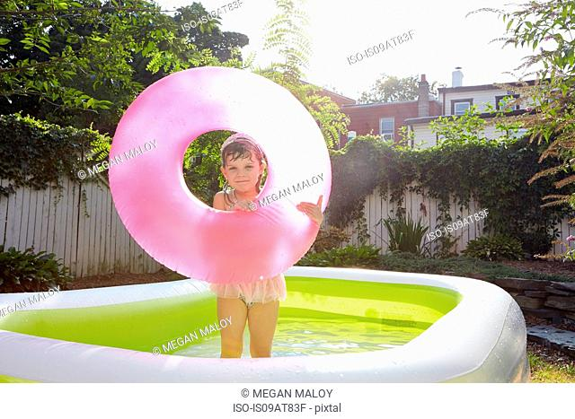 Girl holding up inflatable in pool