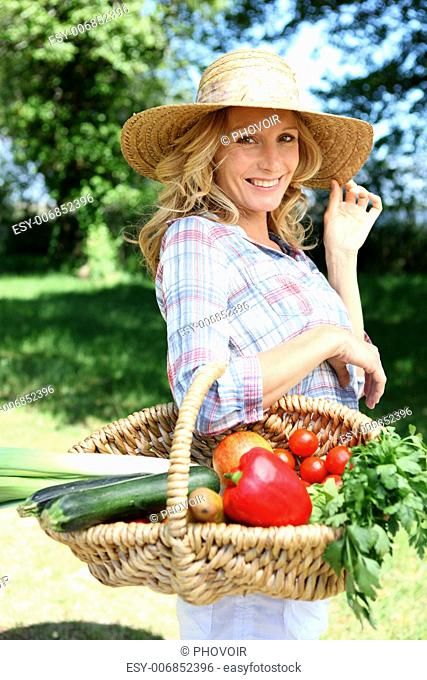 Pretty woman with a straw hat and basket of vegetables