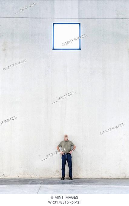 Worker standing under a window in a new warehouse