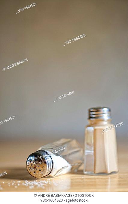 Flipped salt shaker spilling salt next to pepper shaker
