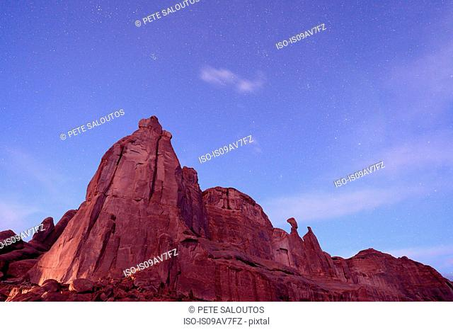 Low angle view of starry sky and rock formations at night, Moab, Utah, USA