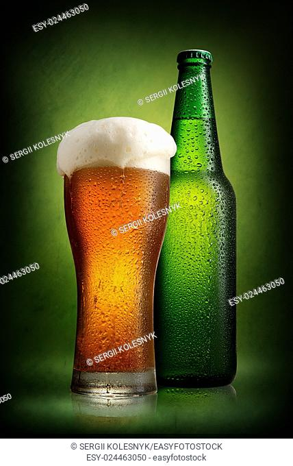 Beer in bottle and tall glass on a green background