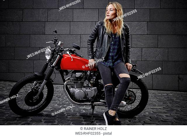 Confident young woman with motorcycle looking away