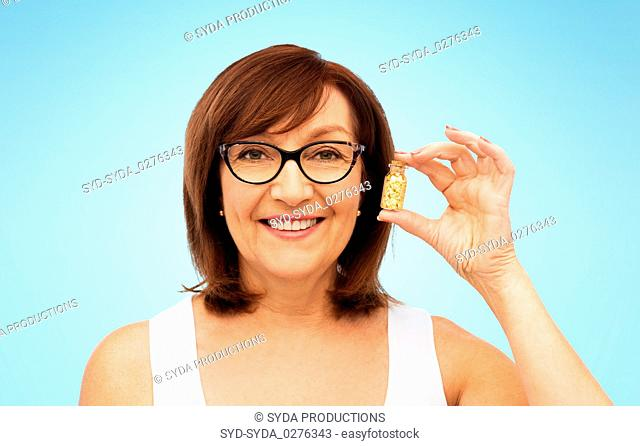 senior woman with gold facial mask in bottle