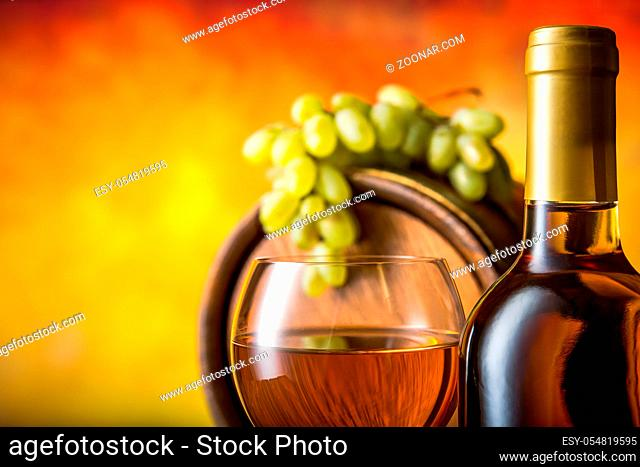 Composition with white wine in cellar on orange background