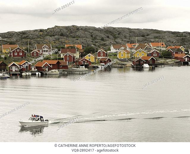 Traditional Scandinavian wooden painted houses with speed boat on the coast at Kabel near Gothenburg, Sweden