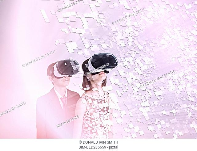 Mixed Race brother and sister using vr goggles