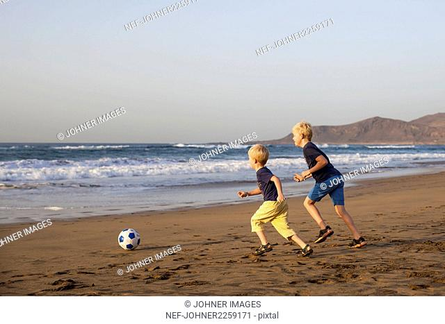 Boys playing soccer on beach