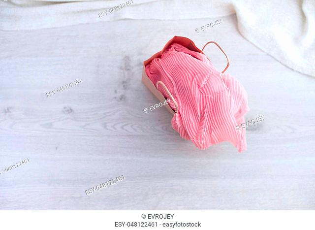 A paper bag with purchases on the wooden light background. Light pink scarf in a paper bag Gift to a woman. Flat lay fashion accessories